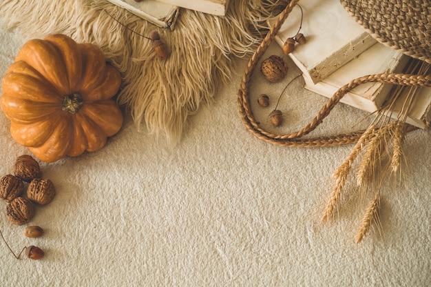 古い本とカボチャ、小麦、サイサリス、ドングリ、クルミの白い暖かい格子縞のヴィンテージストローバッグ。本と読書。秋の気分。秋の時間。居心地の良い秋の装飾 Premium写真
