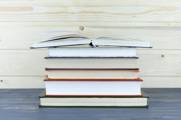 木製の棚の上の古い本。ラベルなし、背骨が空白。 Premium写真