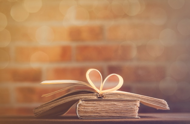Old books on wooden table at fairy lights background Premium Photo