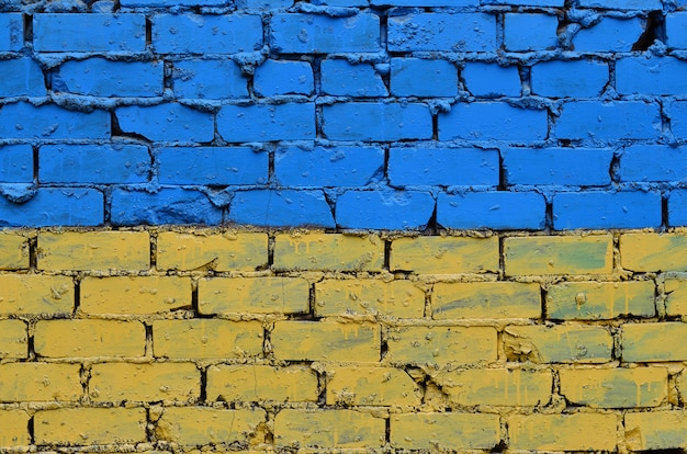 Old brick wall painted in the colors of the ukrainian flag Premium Photo