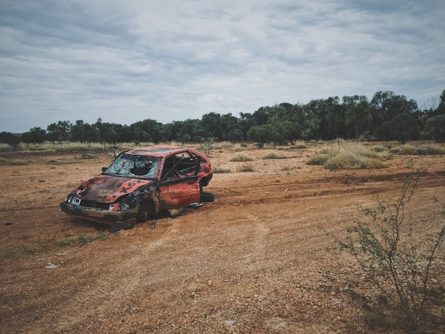 Old broken up car in a dry grass field with trees Free Photo