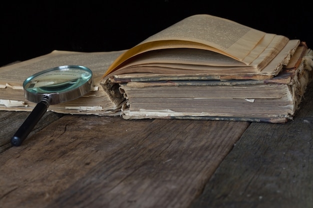 An old brown book and magnifying glass on rustic background. Premium Photo