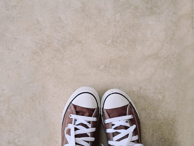 Old brown sneakers, placed on a cement background. Premium Photo