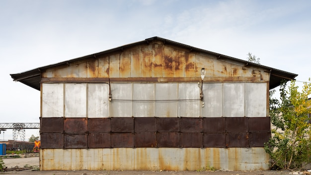 Old brown warehouse with sheet metal cladding with street lights. Premium Photo