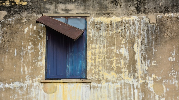 Old brown wooden window at abandoned concrete buildings. Premium Photo