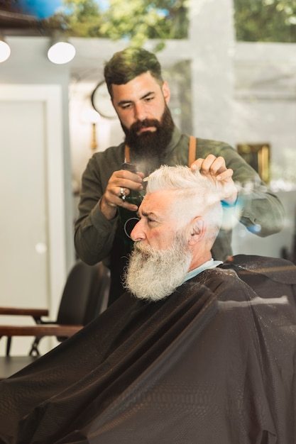 Old brutal customer cutting hair at barbershop Free Photo