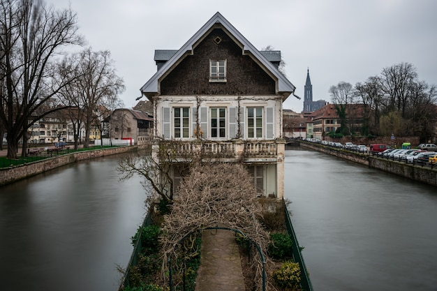 Old building surrounded by water and greenery under a cloudy sky in strasbourg in france Free Photo