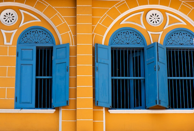 Old building with blue window and yellow buildings Premium Photo