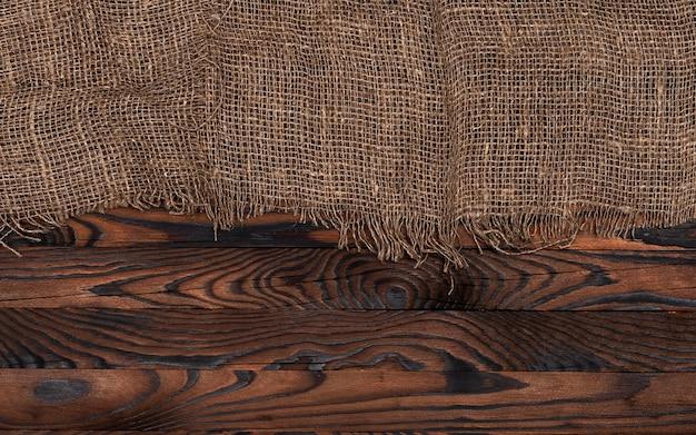 Старая салфетка ткани мешковины на коричневой деревянной предпосылке, взгляд сверху Premium Фотографии