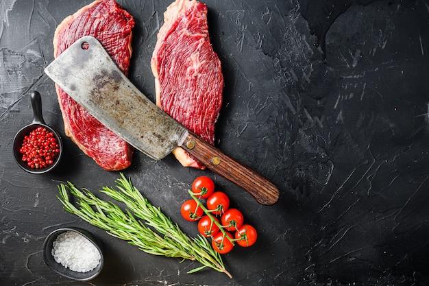 Старый мясник нарезал сырые стейки из говядины пиканья с розмарином, перцем и солью Premium Фотографии