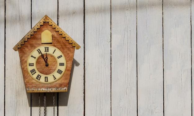 木製の光の壁に古い時計。ヴィンテージ時計。鳩時計。コピースペース。 Premium写真