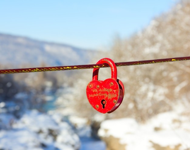 Old closed red padlock in heart shape on winter mountain landscape close up Premium Photo