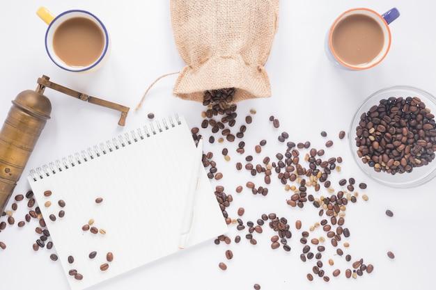 Старая кофемолка; кофейные зерна; чашка кофе; пустой спиральный блокнот с ручкой на белом фоне Бесплатные Фотографии
