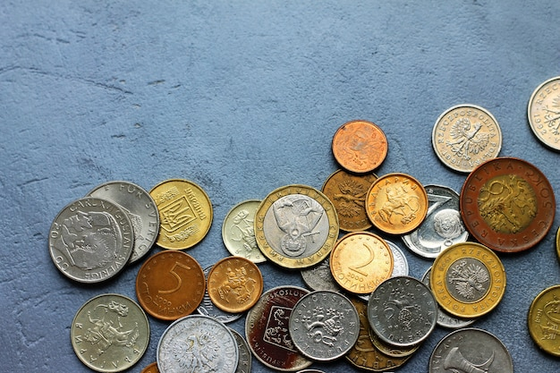 Old coins of different countries on a gray concrete background. Premium Photo