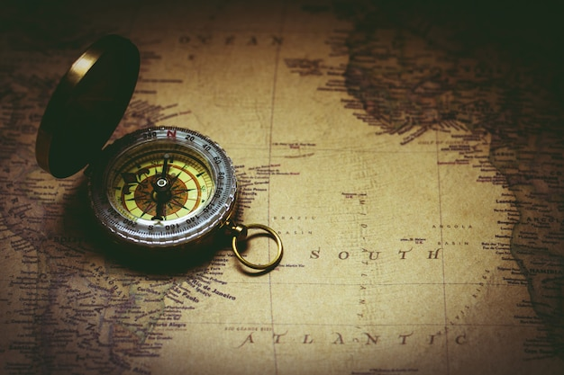 Old compass on antique map Premium Photo