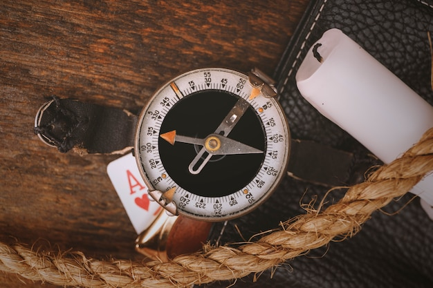 Old compass with rope, candle and card on vintage wood Premium Photo