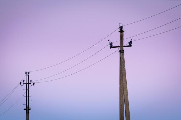 Старые бетонные столбы электричества в сумерках. Premium Фотографии