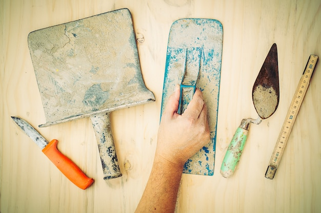 Old construction hand tool with worker hand over white wooden background Free Photo