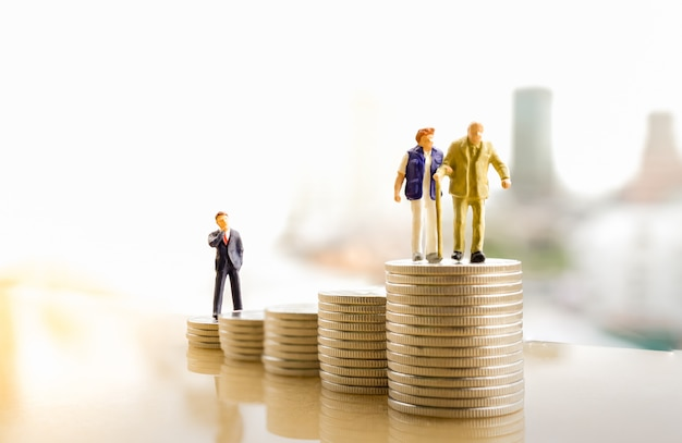 Old couple figure standing on top of coin stack with city backgrounds. Premium Photo