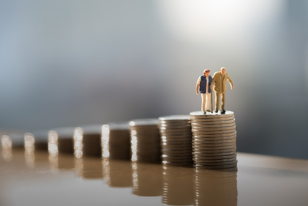 Old couple figure standing on top of coin stack with gray backgrounds. Premium Photo