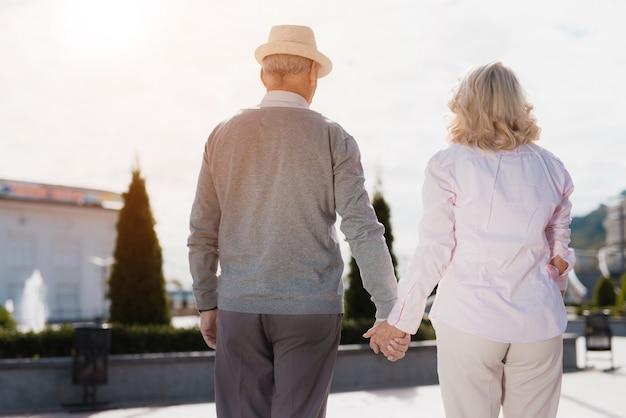 Old couple holding hands. elderly man in hat. Premium Photo