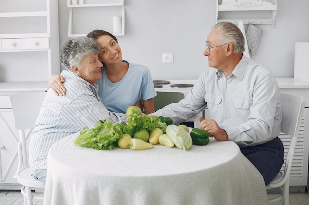 Old couple in a kitchen with young granddaughter Free Photo
