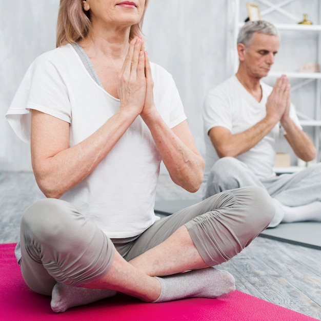 Old couple meditating at home with praying hands Free Photo