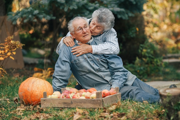 Old couple sittingin a summer garden with harvest Free Photo