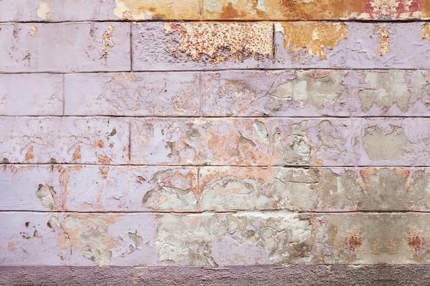 古いひびの入った壁の背景、ライラックとオレンジのペイントテクスチャが欠けています。 Premium写真