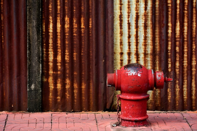 The old and damaged red fire head on pavement Premium Photo