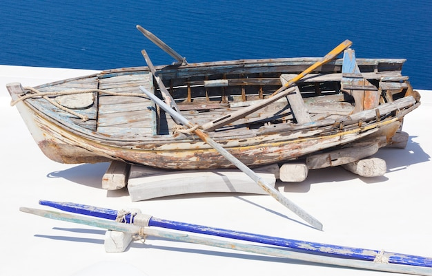 Old damaged rowing boat withpaddles and rope Premium Photo