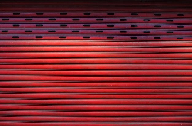 Old detailed aged vintage red textured zinc alloy metal roller shutter door, store front exterior design used in construction industry as building material. Premium Photo