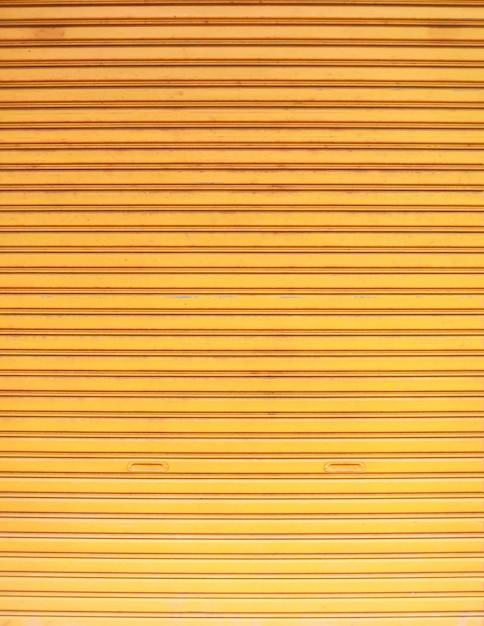 Old detailed aged vintage yellow textured zinc alloy metal roller shutter door Premium Photo