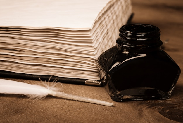 Old diary, an inkwell and a feather Premium Photo