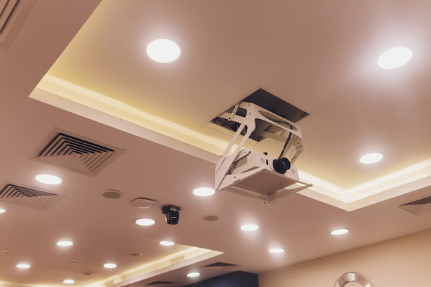Old and dirty projector hang on ceiling in meeting room, education concept. Premium Photo