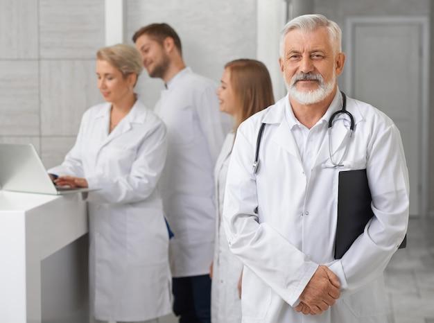 Old doctor posing, medical staff standing behind. Premium Photo