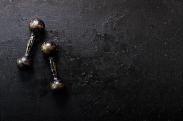 Old dumbbells on concrete background. sport concept. free space for your text. Premium Photo