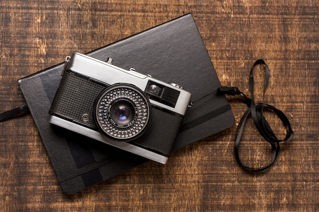 An old-fashioned camera over the closed diary on wooden desk Free Photo