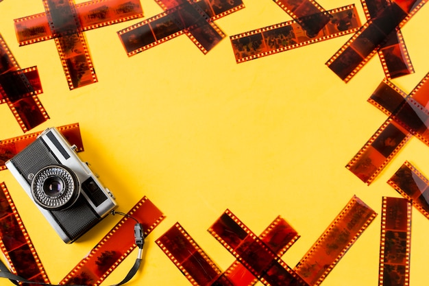 An old fashioned camera with negatives on yellow background Free Photo