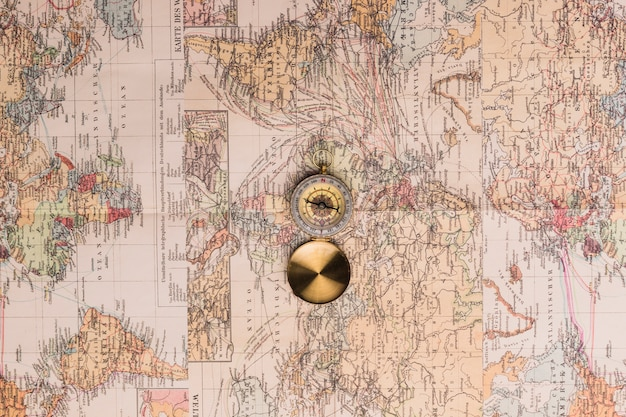 Old fashioned compass on maps Free Photo