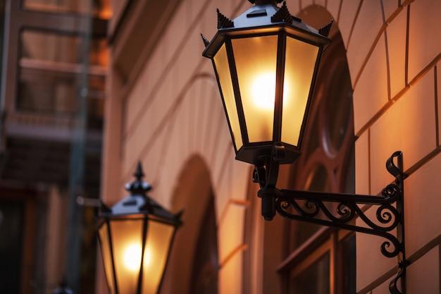 昔ながらの街路灯。夕暮れ時に街灯を明るく点灯。装飾ランプ。街の夕暮れに暖かい黄色の光の魔法のランプ Premium写真