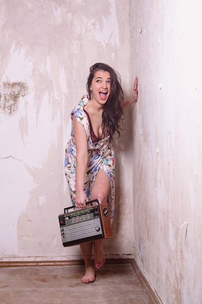 笑顔でラジオを聞いている昔ながらの若い女性 Premium写真
