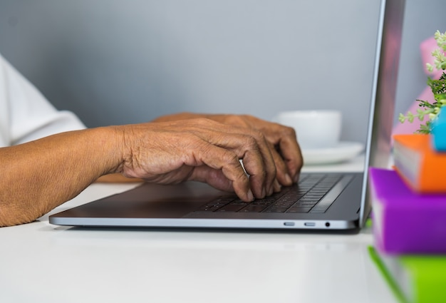 Old female hands typing on laptop keyboard Premium Photo