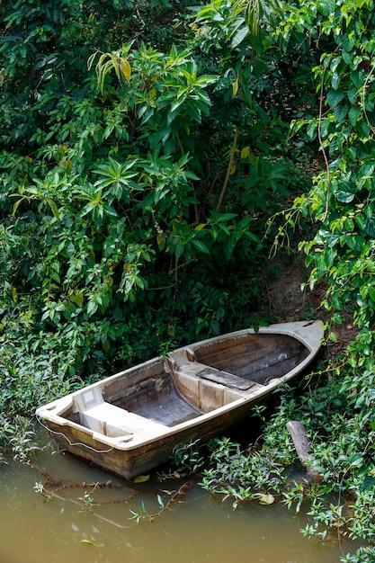 Старая лодка из стекловолокна на якоре на берегу реки Premium Фотографии
