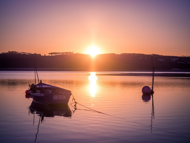 Old fishing boat at the river with the breathtaking view of the sunset Free Photo