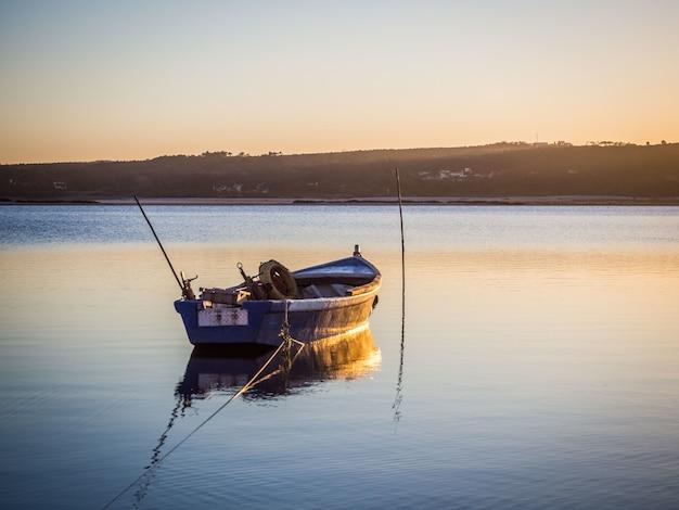 Vecchia barca da pesca sul fiume con la vista mozzafiato del tramonto Foto Gratuite