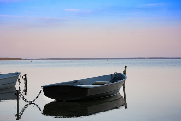 Old fishing boats with chain on lake at sunset Premium Photo