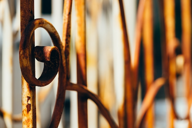 Old forged fence with peeling white paint covered with rust in bright sun close up Premium Photo