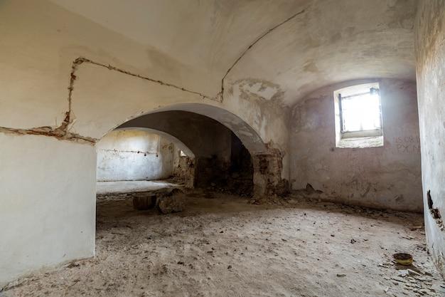 Ruang basement kosong tua bekas bangunan atau istana dengan dinding bata diplester retak, langit-langit melengkung rendah, jendela kecil dengan jeruji besi dan lantai kotor.  Foto Premium