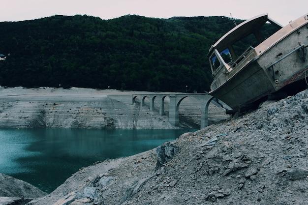 木々に囲まれた水の体にアーチ橋の近くの岩の表面に古い灰色のボート 無料写真